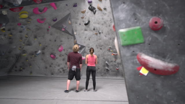 ws dolly shot man and woman staring at a rock climbing wall - climbing wall stock videos & royalty-free footage