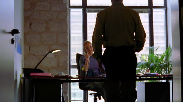 dolly shot man entering office + handing paper to woman sitting at desk / woman talking to man about paper