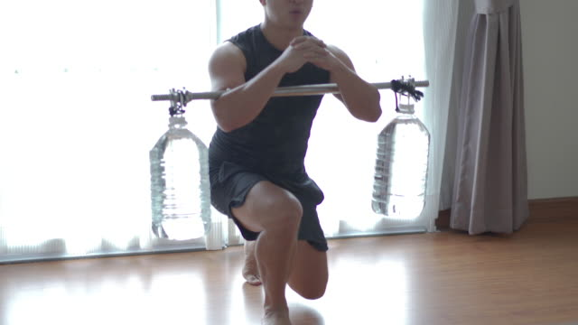 dolly shot man exercising with homemade dumbbell/barbell at home - weights stock videos & royalty-free footage