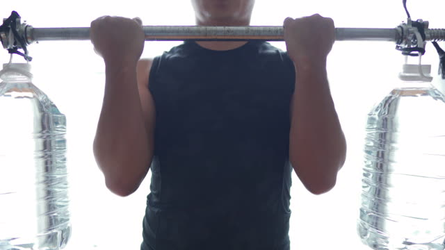 dolly shot man exercising with homemade dumbbell/barbell from plastic water gallon. - fatto in casa video stock e b–roll