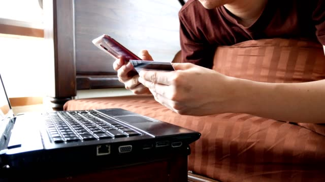dolly shot: man hand holding credit card and using mobile phone in bedroom at home - internet banking or online shopping concept