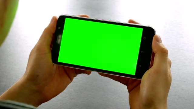dolly shot: man hand using mobile phone with green screen for chroma key at office table - portability stock videos & royalty-free footage
