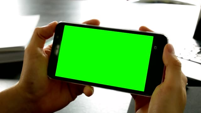 dolly shot: man hand using mobile phone with green screen for chroma key at office table