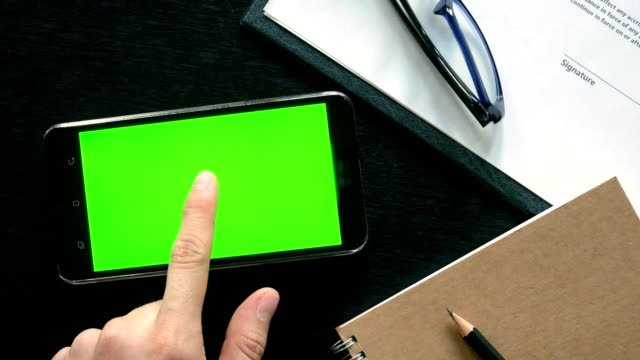 dolly shot: man hand using mobile phone with green screen for chroma key at office table - top view - table top shot stock videos and b-roll footage