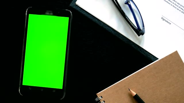 dolly shot: man hand using mobile phone with green screen on office table - top view - table top shot stock videos and b-roll footage