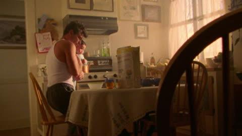 vídeos y material grabado en eventos de stock de dolly shot man holding baby entering kitchen sitting down + pouring cereal at table - desayuno