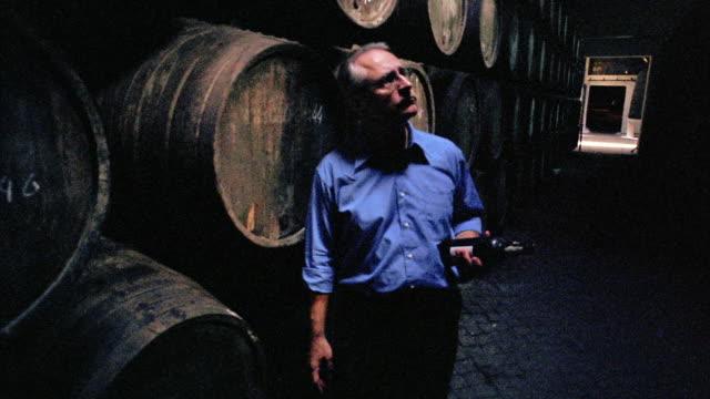dolly shot PAN man holding wine bottle walking past barrels + looking up in wine cellar / Porto, Portugal