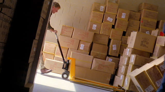 vídeos de stock, filmes e b-roll de canted dolly shot man pumping up hand truck under pallet with two women moving boxes in foreground - pushing