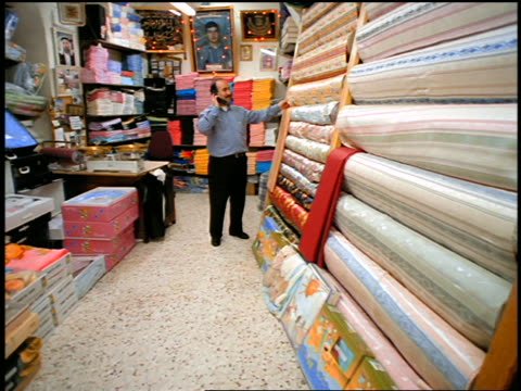 dolly shot man talking on cellular phone in fabric store / muslim quarter, old city, jerusalem - nur männer über 30 stock-videos und b-roll-filmmaterial