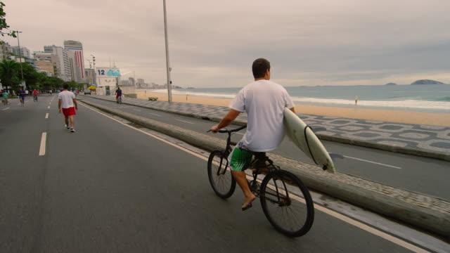 RIO DE JANEIRO, BRAZIL - JUNE 23: Dolly shot, man w/ surfboard, Ipanema Beach June 23, 2013 in Rio