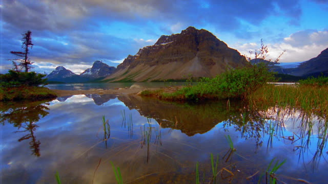 Dolly shot marsh with mountains in background / time lapse with clouds reflecting in water / Banff National Park, Canada