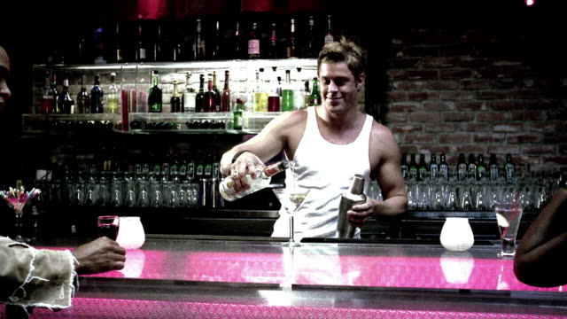 stockvideo's en b-roll-footage met dolly shot medium shot couple join hands and walk away from bar, bartender pushes martini glass forward + poses - martini