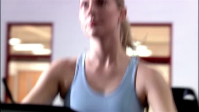 dolly shot medium shot woman using elliptical trainer / being thrown towel / wiping sweat off - ウィスコンシン州アップルトン点の映像素材/bロール