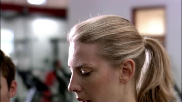 dolly shot medium shot woman using elliptical trainer while trainer looks on - ウィスコンシン州アップルトン点の映像素材/bロール