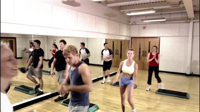 Dolly shot men and women in step aerobics class