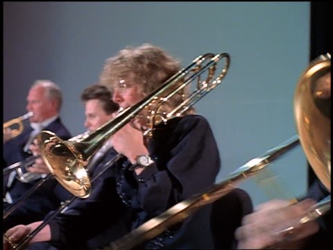 dolly shot men + woman playing trombones in orchestra - classical stock videos & royalty-free footage