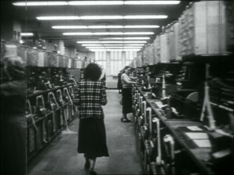 b/w 1956 dolly shot men + women operating rows of telegraph machines in large room - telegraph machine stock videos & royalty-free footage