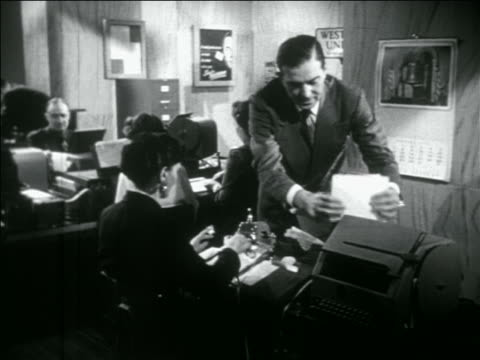 b/w 1956 dolly shot men + women working in busy western union telegraph office - telegraf stock-videos und b-roll-filmmaterial
