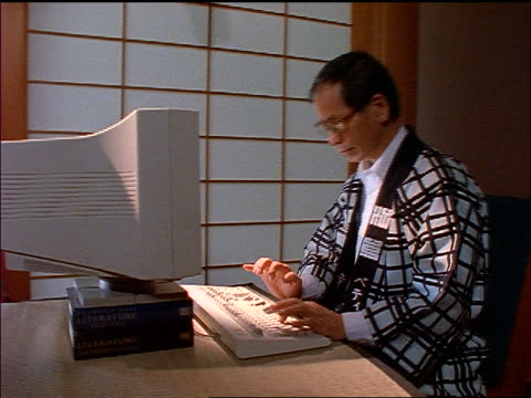 dolly shot middle aged asian man in robe typing on computer - 中年の男性一人点の映像素材/bロール