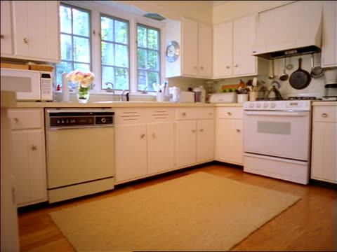 dolly shot modern + light colored empty kitchen in house - lavastoviglie video stock e b–roll