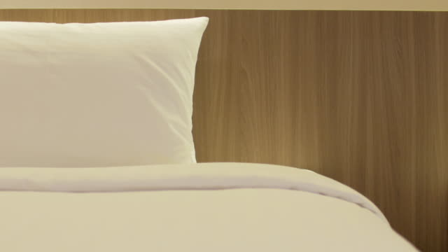 dolly shot movement of bedroom close up to bed and pillow - lampada elettrica video stock e b–roll