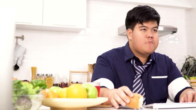 vidéos et rushes de dolly tourné: pas beaucoup temps, thai en surpoids homme d'affaires en train de déjeuner tout en travaillant sur l'ordinateur à son domicile - désespoir