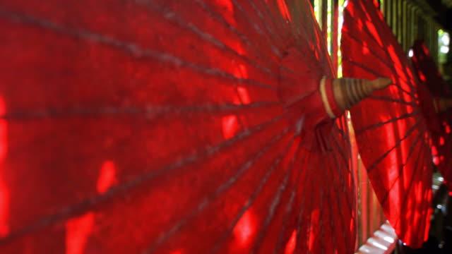 dolly ha girato l'artigianato degli ombrelli di carta della thailandia settentrionale in mostra. - ombrello video stock e b–roll