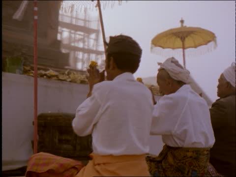 vídeos de stock e filmes b-roll de dolly shot of 3 men praying at hindu temple outdoors / kintamani, bali / indonesia - só homens maduros