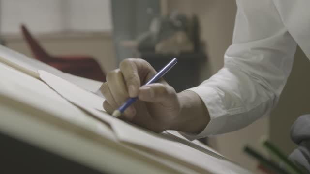 vídeos de stock, filmes e b-roll de dolly shot of a designer drawing a sketch on a paper - prancheta