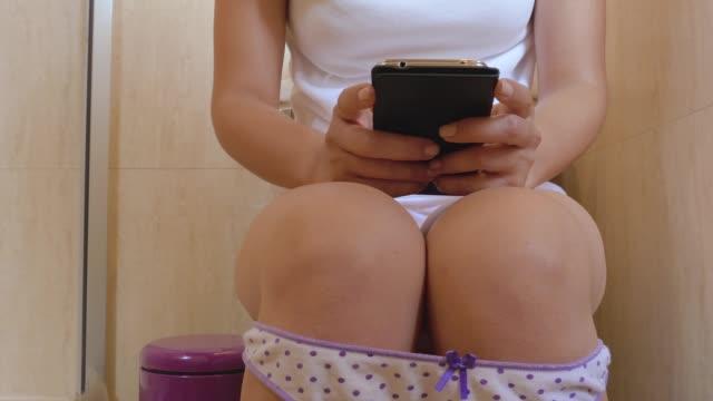 dolly aufnahme einer hispanic junge frau mit smartphone in der toilette - underwear stock-videos und b-roll-filmmaterial