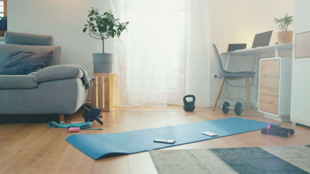 ds dolly shot of a living room ready for a home stretching and exercising. - exercise equipment stock videos & royalty-free footage