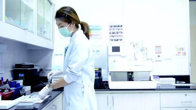 ドリー ショット大人の女性科学者が研究室での作業の - 研究点の映像素材/bロール