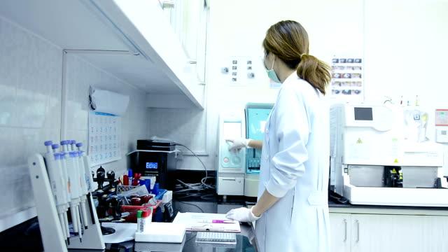 dolly-schuss von erwachsenen weiblichen wissenschaftler arbeiten im labor - phiole stock-videos und b-roll-filmmaterial