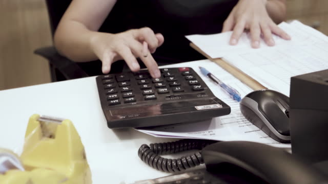 dolly shot of asian woman calculating in home - home economics stock videos & royalty-free footage