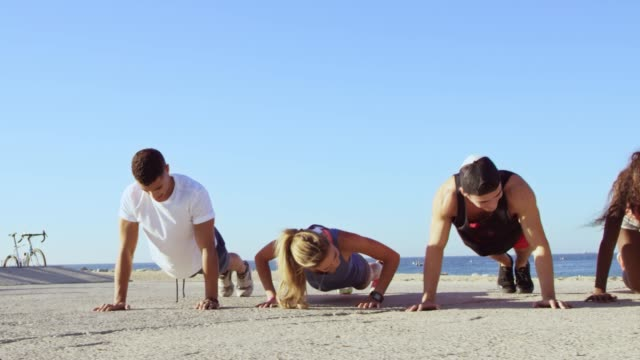 dolly shot of athletes doing push-ups at beach - sports team stock videos & royalty-free footage