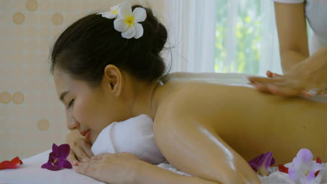 dolly shot of beautiful asian woman enjoying massage therapy with essential oils - massage oil videos stock videos and b-roll footage