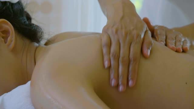 stockvideo's en b-roll-footage met dolly schot van mooie aziatische vrouw genieten van therapie van de massage met essentiële oliën - beauty spa