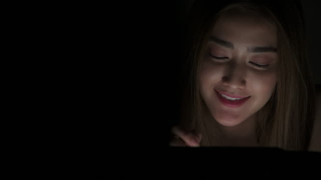dolly shot of beautiful asian woman using digital tablet in bedroom at night. - columnist stock videos & royalty-free footage