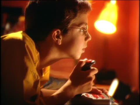 stockvideo's en b-roll-footage met dolly shot of boy using joystick playing video game (blank screen) - wit scherm