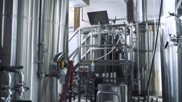 stockvideo's en b-roll-footage met dolly shot of brewer working by storage tanks in brewery - kwaliteit