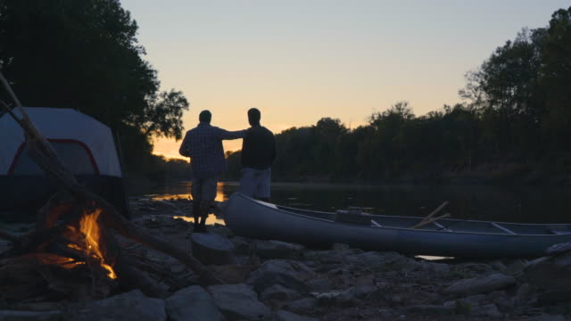 dolly shot of burning campfire by father and son standing at lakeshore during sunset - young men stock videos & royalty-free footage