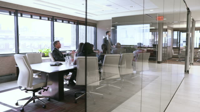 dolly shot of business people discussing in board room seen through glass - dolly shot stock videos & royalty-free footage