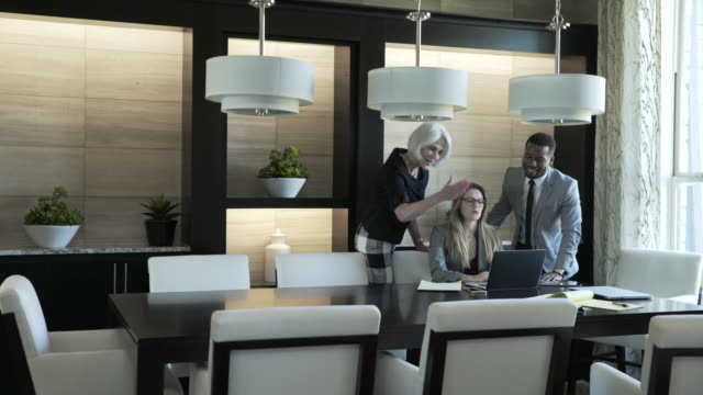 dolly shot of business people discussing over laptop computer in meeting at board room - colleague stock videos & royalty-free footage