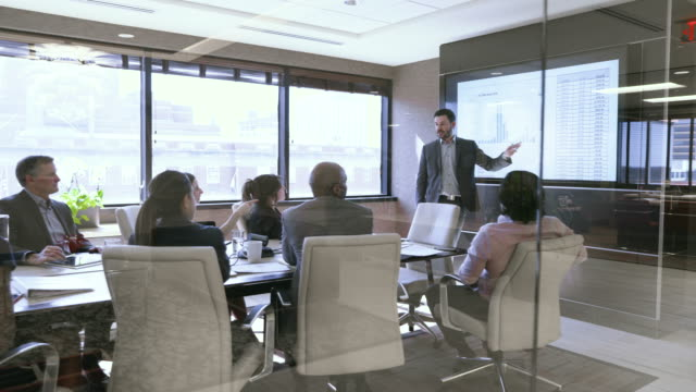 dolly shot of business people in meeting at board room seen through glass - dolly shot stock videos & royalty-free footage