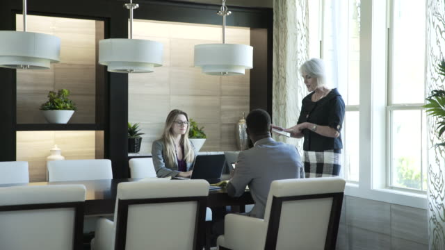 dolly shot of businesswoman explaining colleagues over tablet computer in meeting at office - wide shot stock videos & royalty-free footage