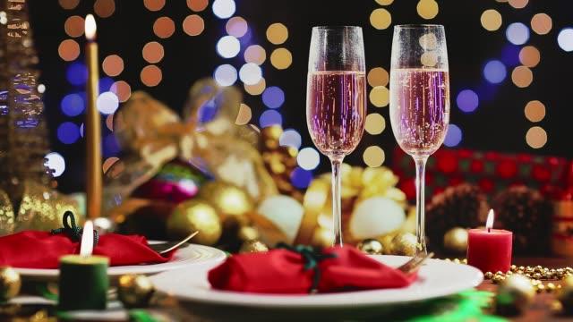 シャンパンのドリー ショットは、ゴールデン休日背景に 2 つのテーブルのフルートします。クリスマスと新年のお祝い - お食事デート点の映像素材/bロール
