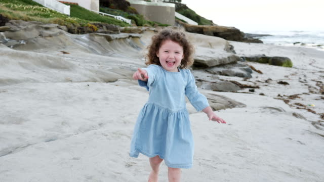 dolly shot of cheerful girl pointing while running at beach - pointing stock videos & royalty-free footage