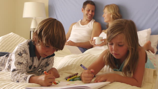 dolly shot of children drawing in bed while parents watch/marbella region, spain - brother stock videos & royalty-free footage