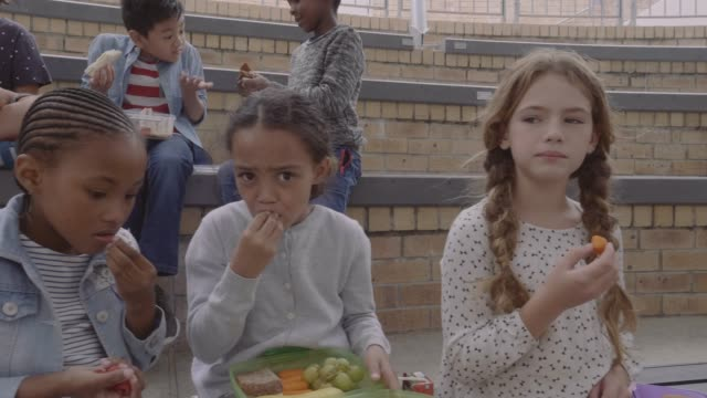 dolly shot of children eating during lunch break - lunch stock videos & royalty-free footage