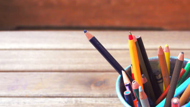 4k: dolly shot of colored pencils on a wooden table - pastello video stock e b–roll
